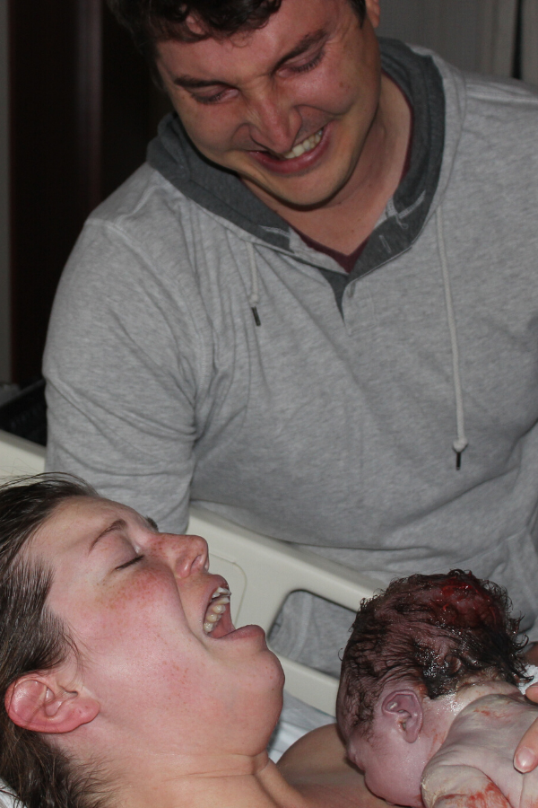 Triumphant birthing parent holding baby with other parent smiling; what birth looks like fully supported by a birth doula